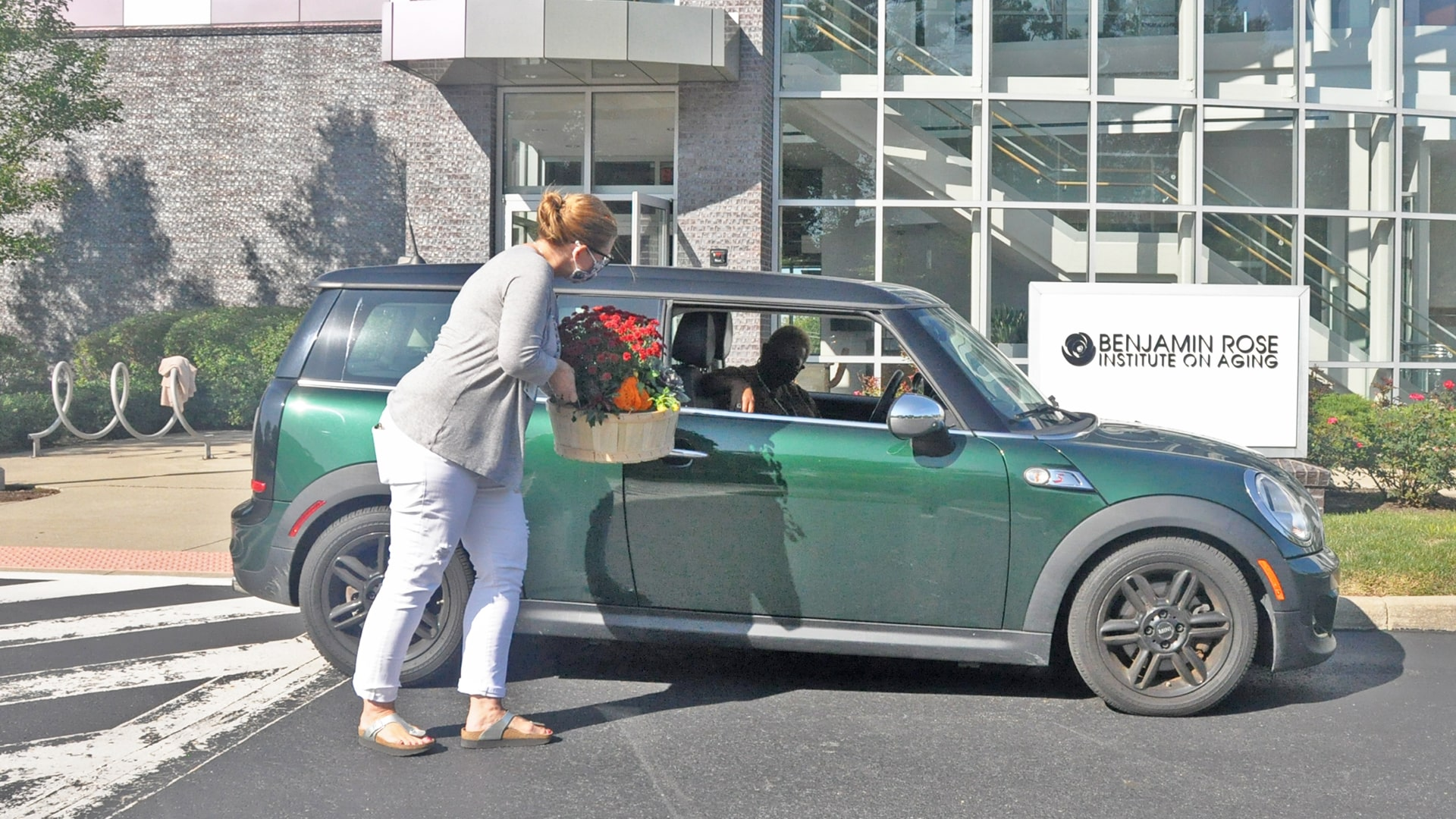 Masked Benjamin Rose staff handing a customer in a car their bountiful basket